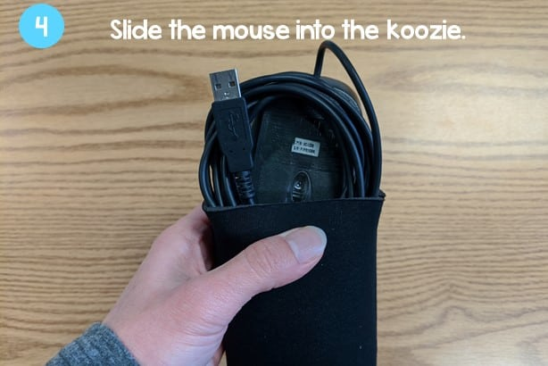 hand putting the computer mouse neatly into the can koozie